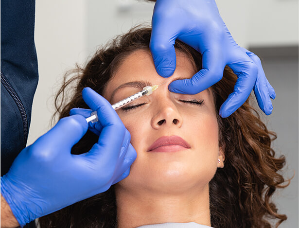 Gloved Hands Applying Forehead Injectables
