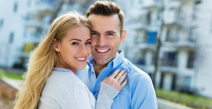 smiling lovable couple in front of camera