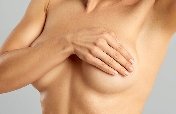woman covering breast with one hand
