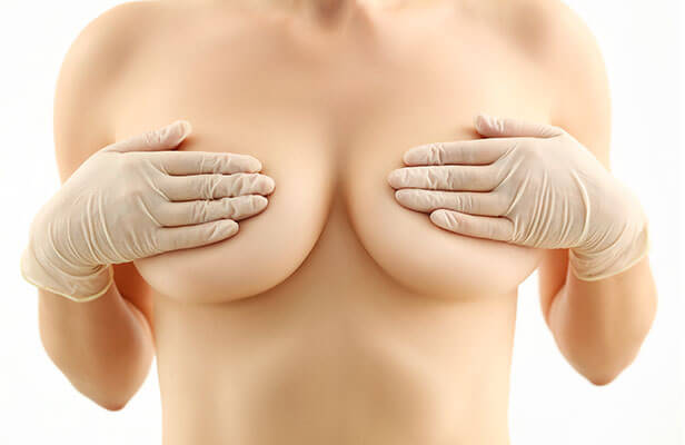 woman wearing gloves covering her breast