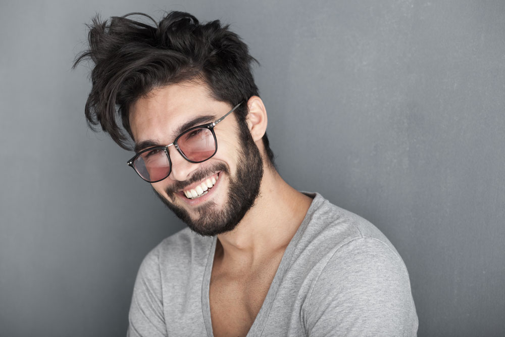 Sexy-man-with-beard-smiling-against-big-wall-