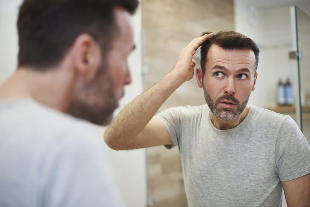 man in front of mirror checking his hair