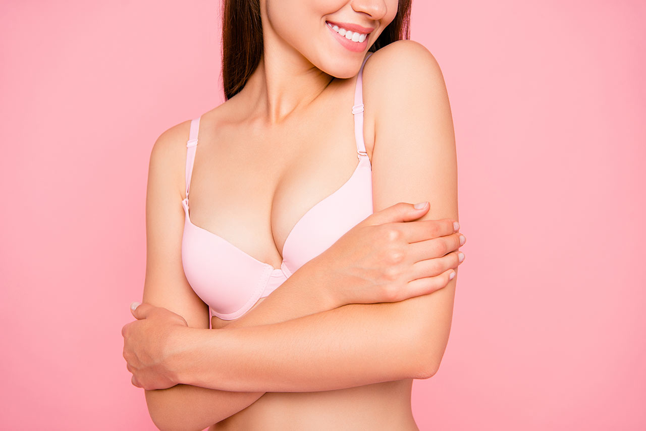Woman smiling & cradling breasts