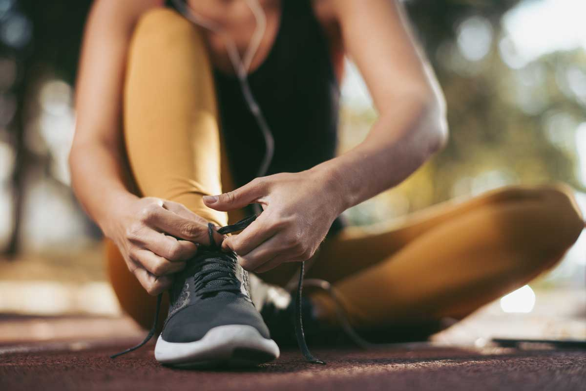 fitness woman sitting tying her shoelace