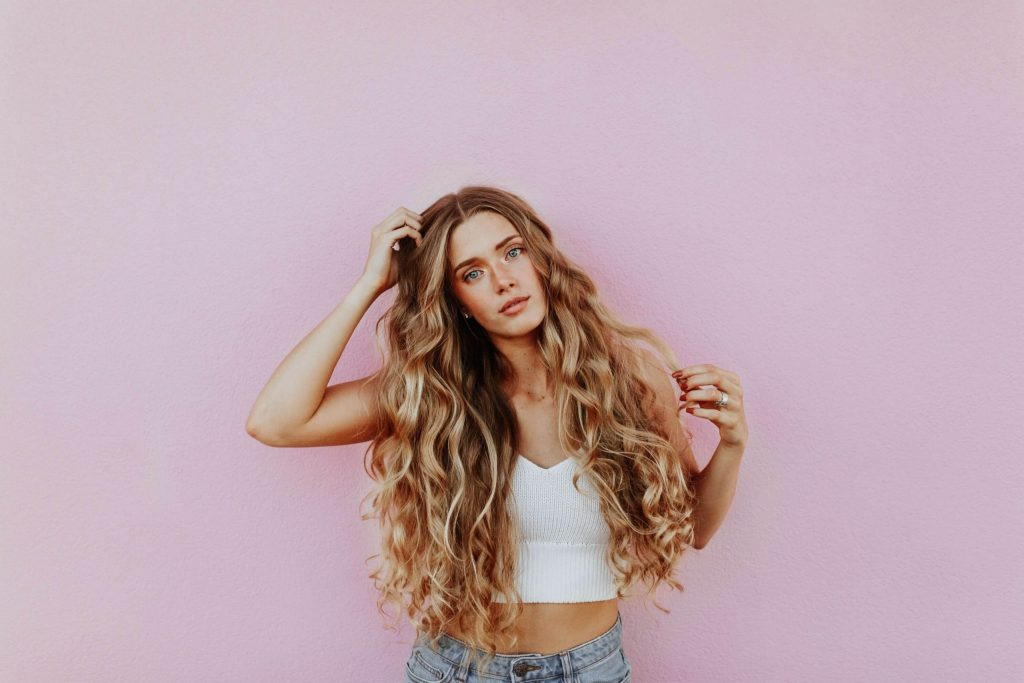Blonde woman with long hair in front of pink wall