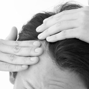 Greyscale photo of man parting hair