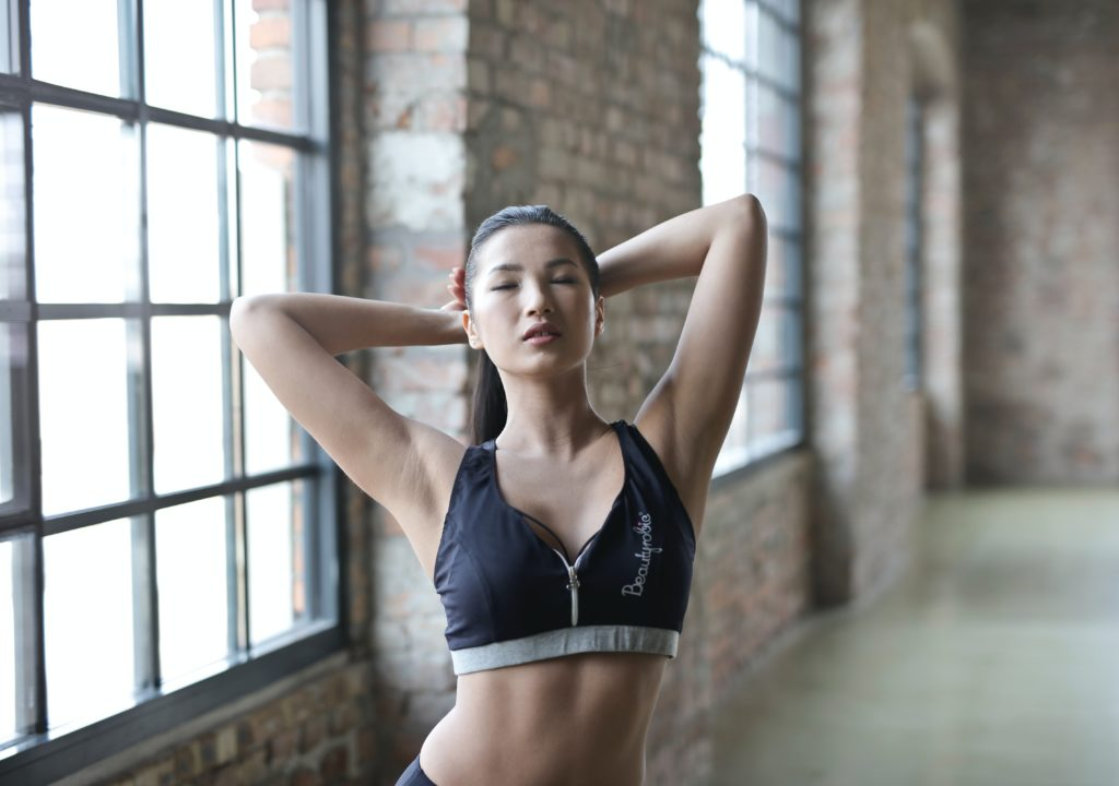 Athletic woman in sports bra poses in front of brick wall