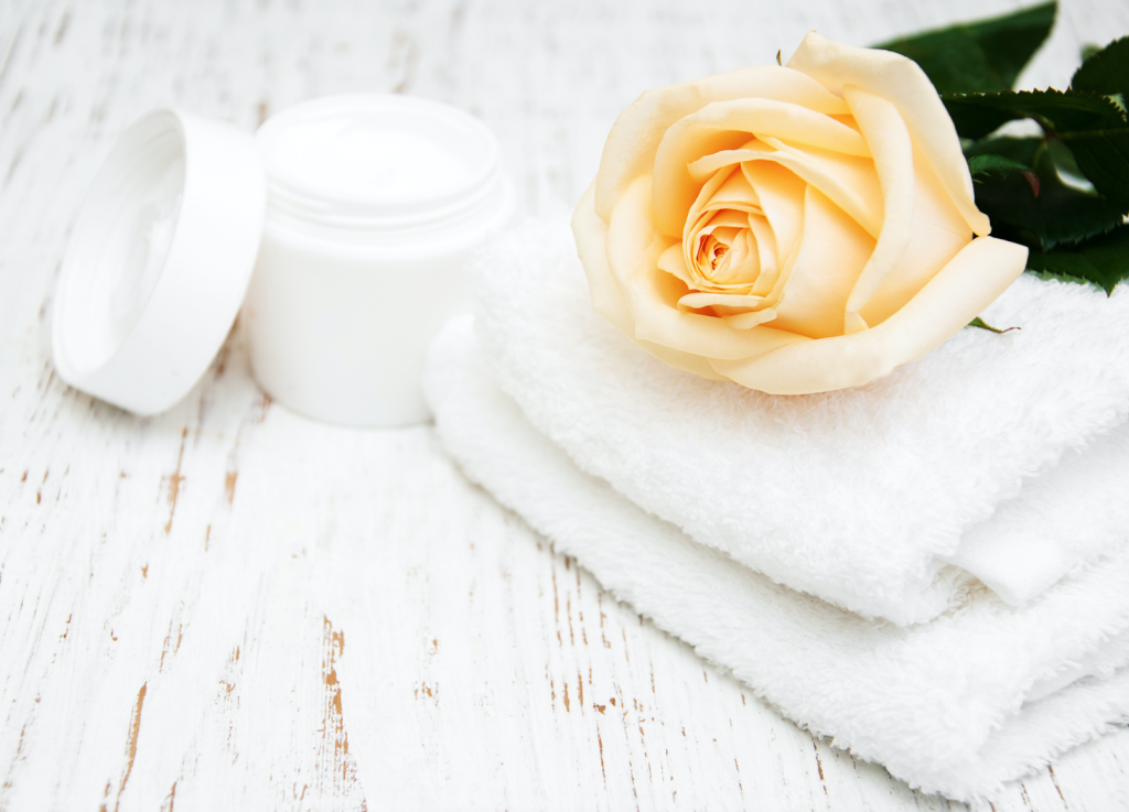 Towel, moisturizer, and rose on a table