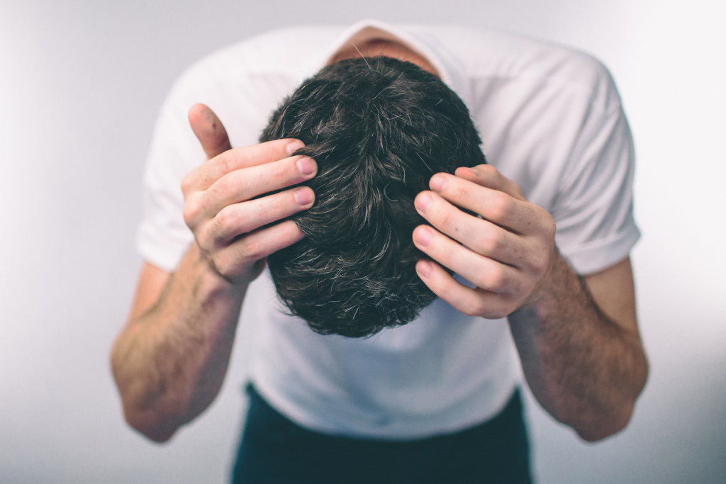 Man bending over and parting his full head of black hair