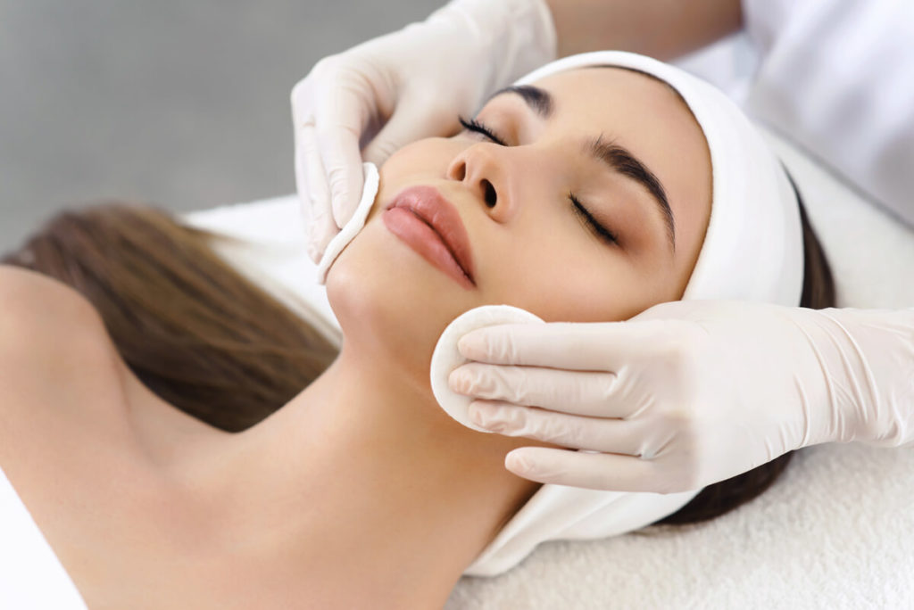 Woman with closed eyes receiving a facial treatment