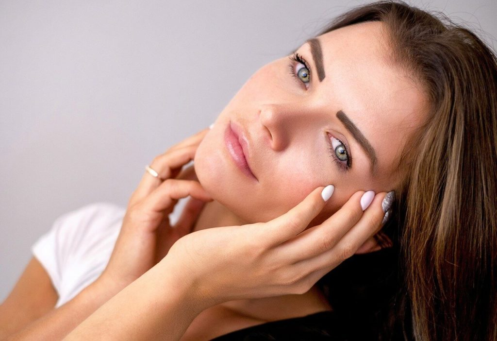 brown haired girl holds face with manicured nails