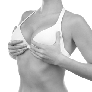 Woman in White Bra Holding Breasts