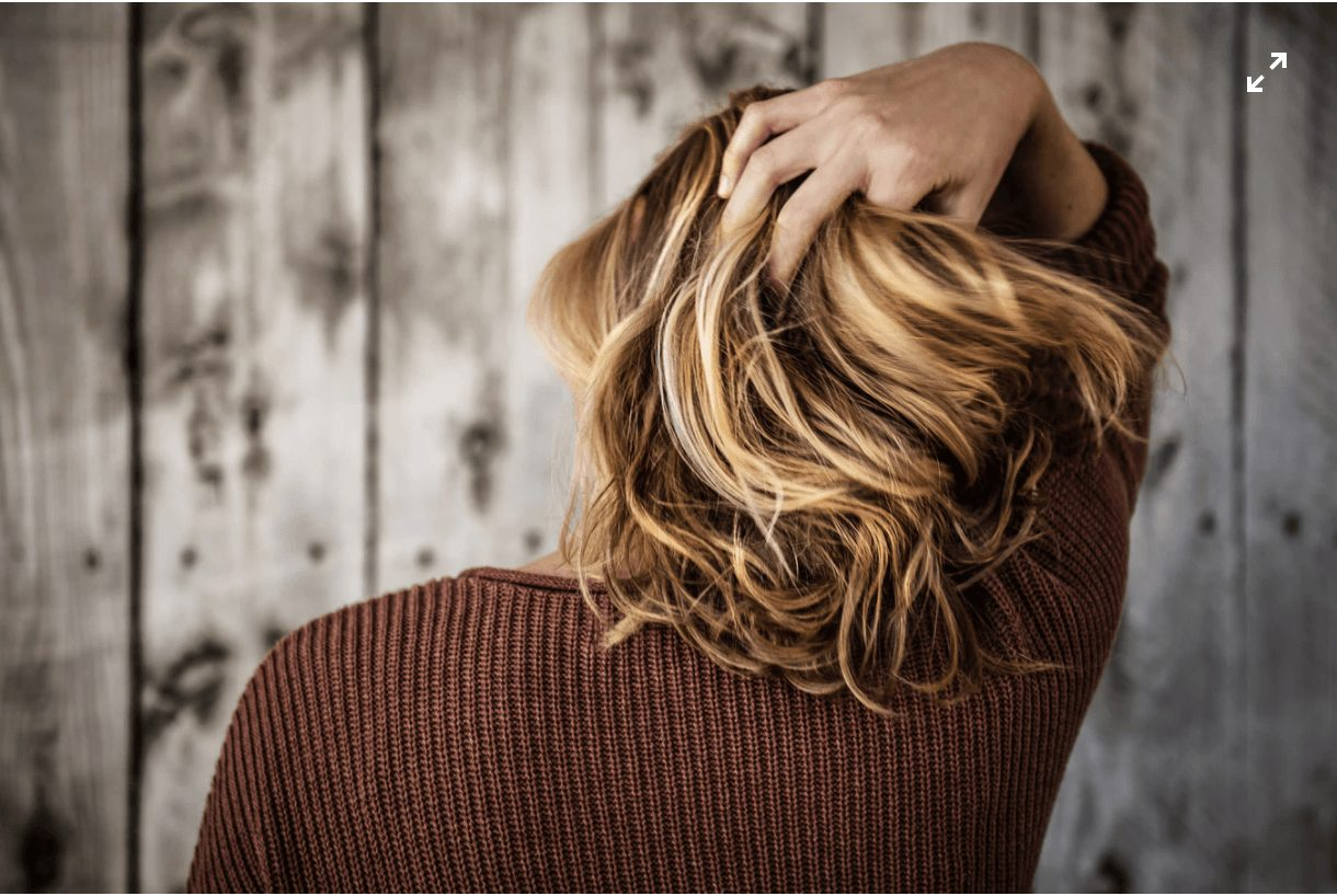 A woman combs her hand through her hair from behind