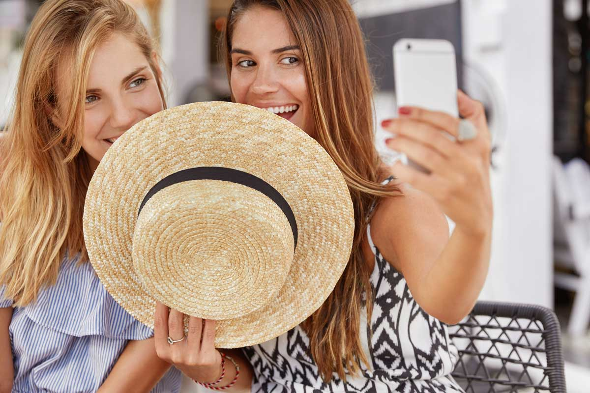 two women hiding behind hat