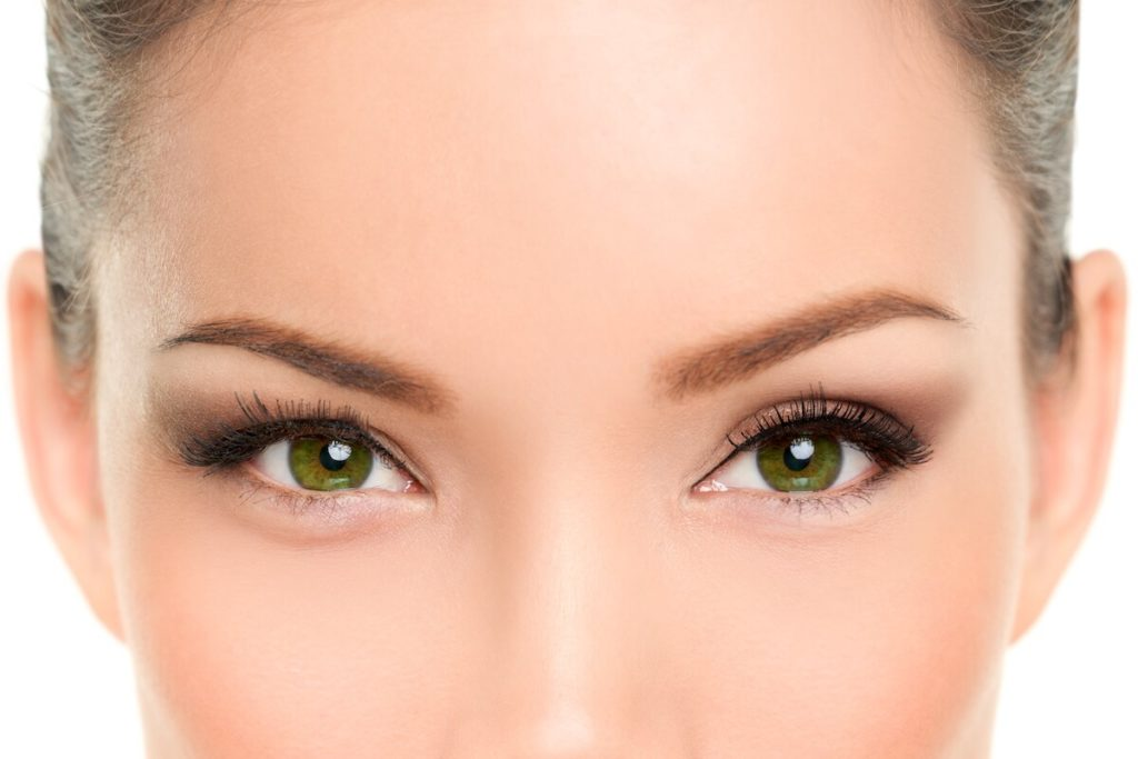close up of a beautiful woman's green eyes and forehead