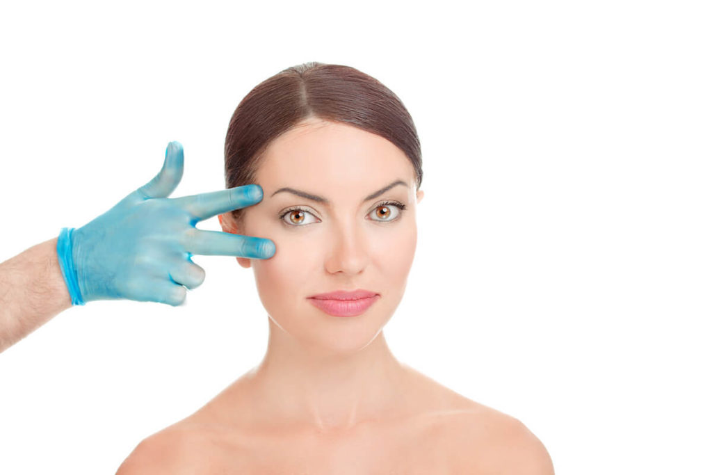 a plastic surgeon touches a woman's temples