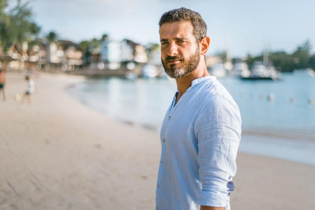 A man on the beach wearing white