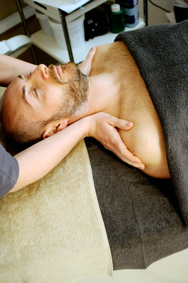 A man reducing stress lying on a massage table