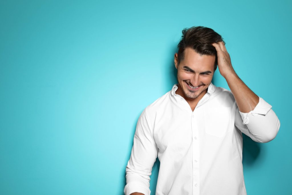 Smiling man who went to a hair transplant surgeon