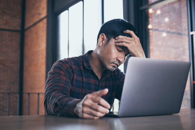 A stressed man with his hand in his hair looking at a laptop