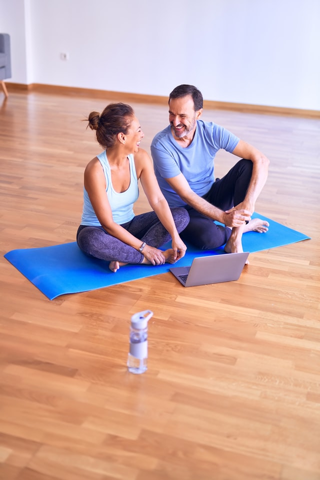 A couple laughing on a yoga mat