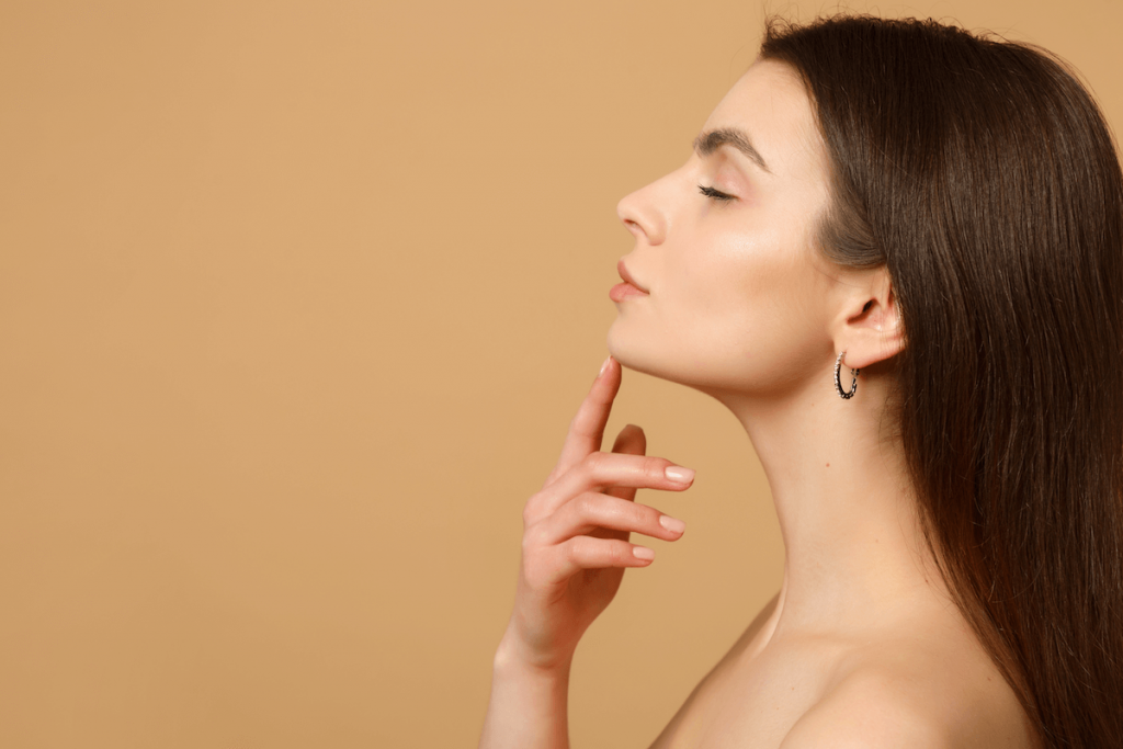 A brunette woman with a strong, youthful jawline, neck, and clear skin touches her chin in profile