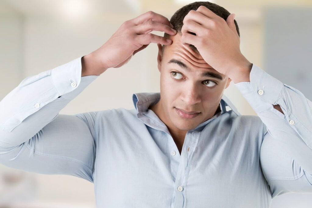 Man checking hairline