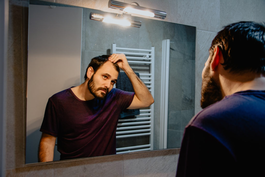Man looking into a mirror, worried about his hair