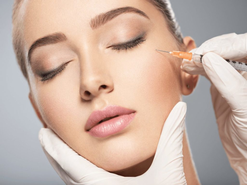 A woman receiving a cosmetic injection of Botox near the eyes