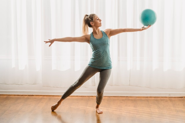 a young woman exercising with a sports ball