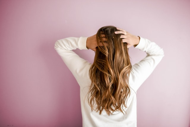 woman gently brushing long hair with hands