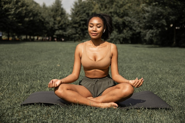 a woman doing yoga in a park