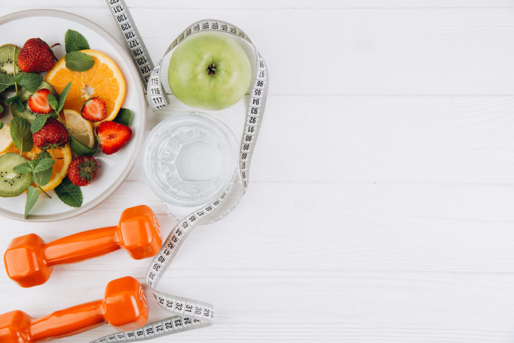 Healthy fruits on a table with barbells and a tape measure