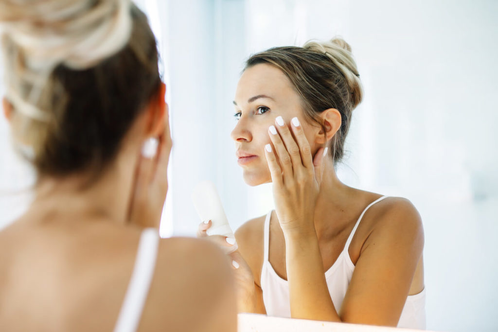 A woman in a white camisole examines her face in a mirror