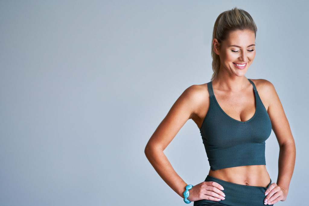 A fit woman in gray athletic wear smiles with hands on her hips